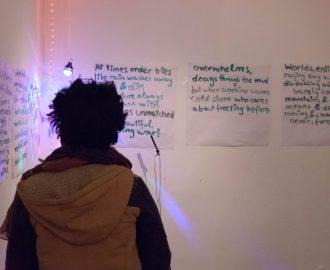 Bild aus der Ausstellung: BLACK EXCELLENCE - eine Person von hinten steht vor einem ausgestellten Text @ Abiona Esther Ojo